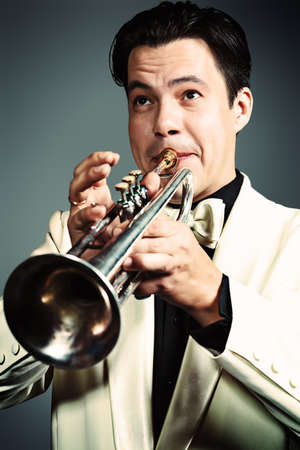brass instrument: Portrait of a musician playing the trumpet at studio.  Stock Photo