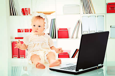 Beautiful baby is playing with laptop at home. Isolated over white. photo