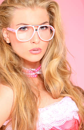 Portrait of a charming blonde woman in pink spectacles posing in studio over pink background. photo