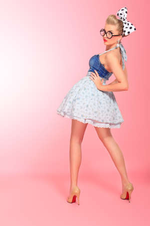50s fashion: Beautiful young woman with pin-up make-up and hairstyle posing over pink background. Stock Photo