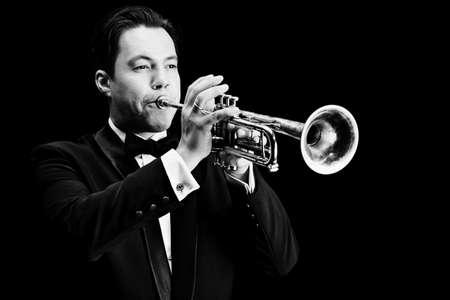 trompeta: Retrato de un m�sico que toca la trompeta. Fondo negro.