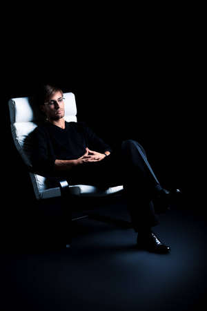 Handsome man is sitting in the armchair over black background. Stock Photo - 14870843