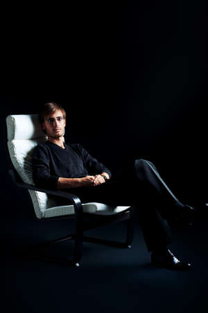 Handsome man is sitting in the armchair over black background. Stock Photo - 14870826
