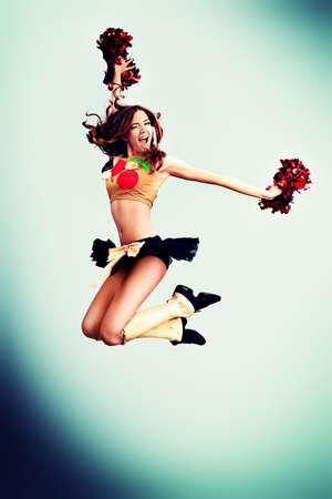 adult cheerleader: Beautiful girl cheerleader jumping in victory. Studio shot.