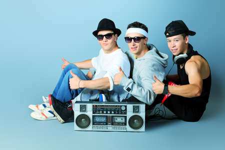 Group of trendy teenagers posing with boombox at studio. Stock Photo - 15195685