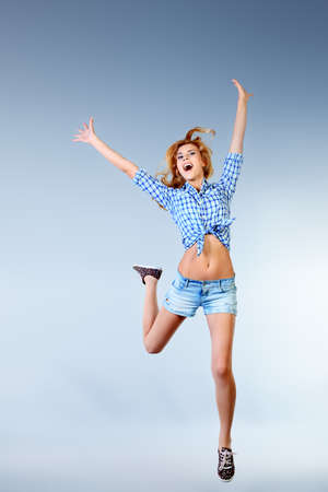 Portrait of a happy young woman jumping at studio.  photo