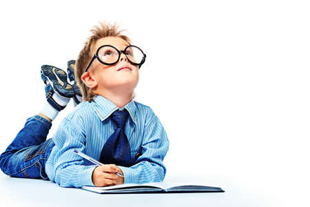 Little boy in spectacles and suit lying on a floor with a diary. Isolated over white background. Stock Photo