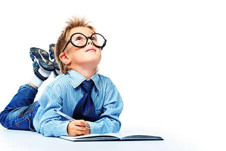 niños pensando: Niño pequeño con gafas y traje tendido en el suelo con un diario. Aislado sobre fondo blanco.