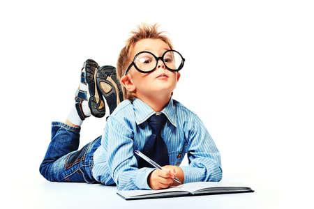 Kleine jongen in brillen en pak liggend op een vloer met een dagboek. Geà ¯ soleerd op witte achtergrond.
