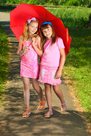 Two cheerful girls with umbrella at the summer park. photo