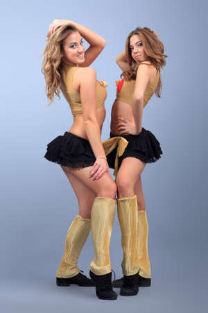 Two professional cheerleaders posing at studio.  photo