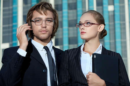 Business woman and business man is talking on mobile phone in front of skyscrapers.  Stock Photo - 14972945