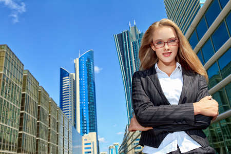 ceo: Smiling young business woman standing on the street of the big city.