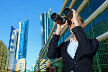 new look: Business woman standing in the big city and purposefully looking through the binoculars.  Stock Photo