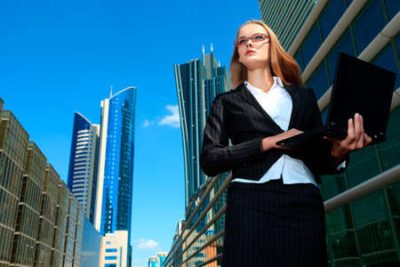 big woman: Young business woman standing with laptop in the big city and purposefully looking away.
