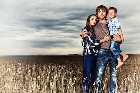 familia abrazo: La familia feliz de pie juntos en el campo de trigo sobre el cielo nublado hermoso.