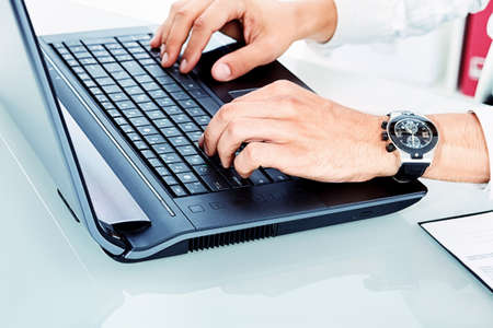 Close-up of male hands typing on the laptop. photo