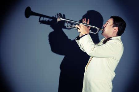 trompeta: Retrato de un m�sico que toca la trompeta en el estudio. Foto de archivo