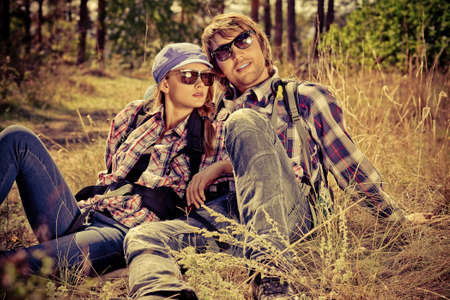 fashionable sunglasses: Casual young couple sitting together on a grass on a sunny day.