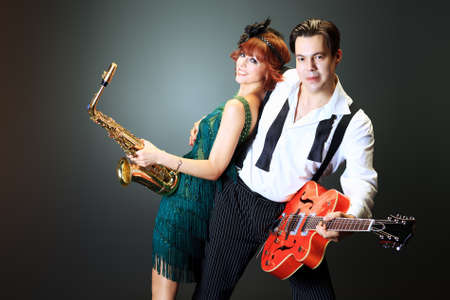 Couple of professional musicians in retro style posing in costumes at studio. photo