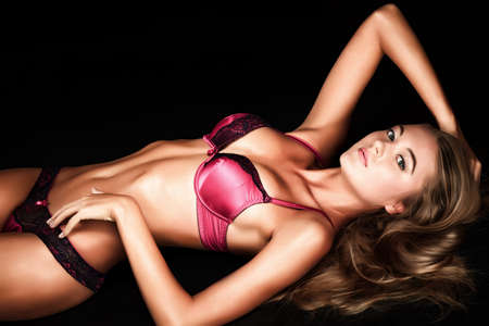 Portrait of a sexual woman in lingerie over black background. Stock Photo