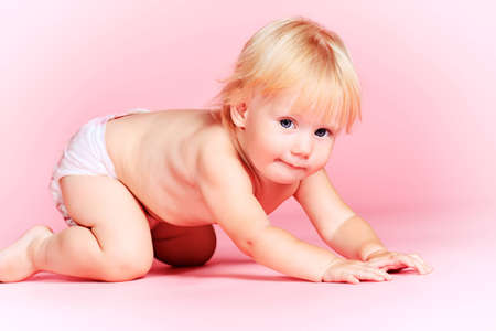 Lovely baby girl sitting on a floor. Over pink background. Stock Photo - 15017913