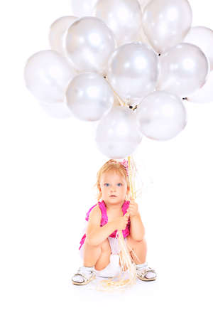 Happy little girl holding a lot of balloons. Isolated over white background. Stock Photo - 15007561
