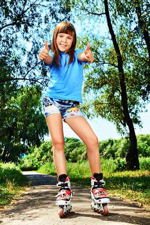 niño en patines: Linda chica en patines de ruedas en un parque de verano.