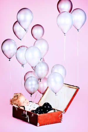 Little boy is sleeping in the old suitcase under many balloons.  Stock Photo - 15007574