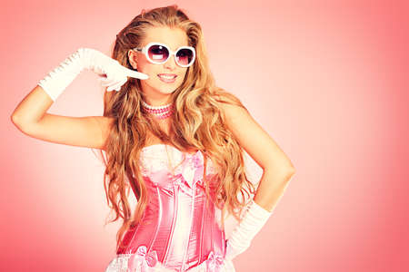 Portrait of a charming blonde woman posing in studio over pink background.