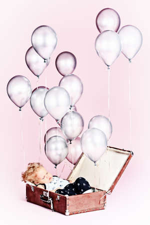 Little boy is sleeping in the old suitcase under many balloons. Stock Photo - 15007595