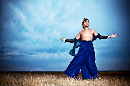 Fashionable male model posing in the field over stormy evening sky. photo