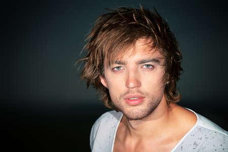 belleza masculina: Retrato de un modelo masculino hermoso que presenta en el campo sobre el cielo de la noche tormentosa. Foto de archivo