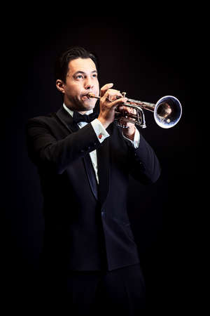 Portrait of a musician playing the trumpet. Black background.