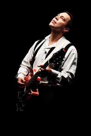 Portrait of a professional artist playing on guitar. Over black background. Stock Photo - 15023121