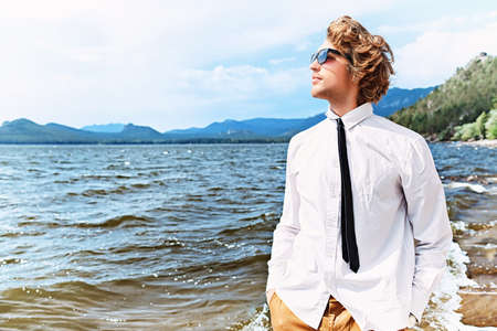purposeful: Handsome business man standing on a seaside and looking into the distance.