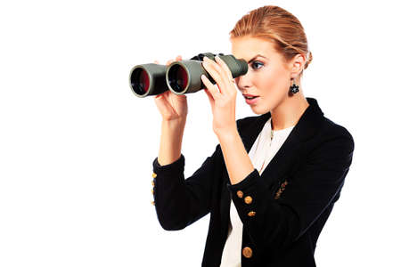 Beautiful young woman in business suit looking through binocular. Isolated over white background. photo