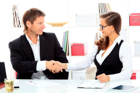 consensus: Business woman and businessman shaking hands at the meeting in the office.