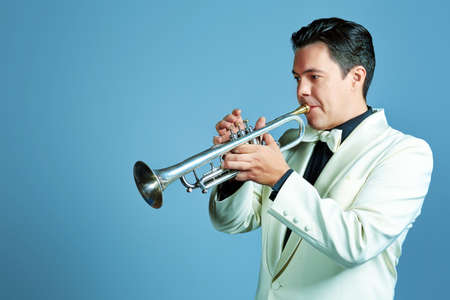 trumpeter: Portrait of a musician playing the trumpet at studio.  Stock Photo