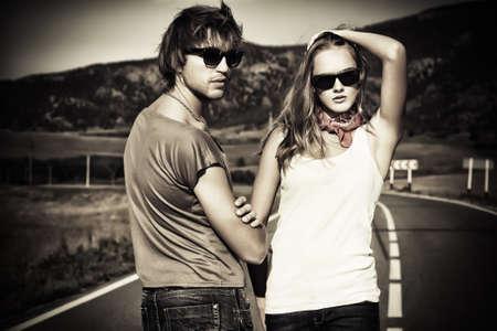 fashionable couple: Pareja de j�venes modernos que presenta en una carretera sobre el paisaje pintoresco.
