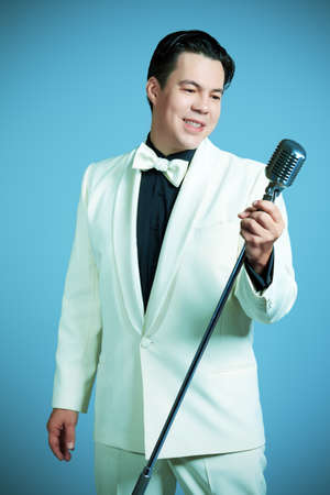 singer: Portrait of a man professional singer in retro style posing in costume at studio.