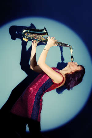 saxophonist: Professional musician posing with her saxophone at studio.