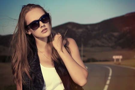 Beautiful young woman posing on a road over picturesque landscape. photo