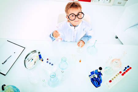 Cute boy is making science experiments in a laboratory. Education. photo