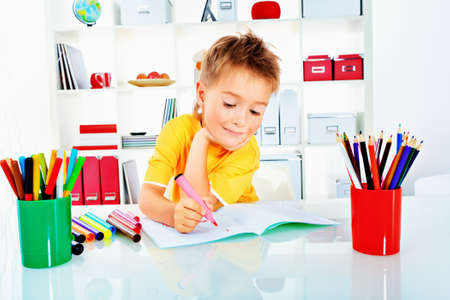 Little boy drawing in his notebook at home. Stock Photo - 15333128