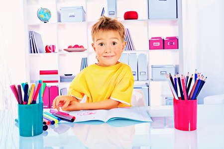 Little boy drawing in his notebook at home. Stock Photo - 15503420