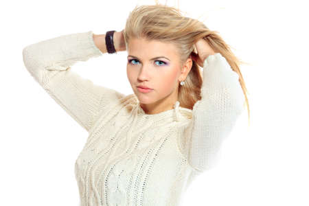 Portrait of a pretty blonde girl in warm sweater. Isolated over white. photo