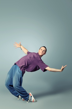 Trendy young man dancing hip-hop at studio. photo