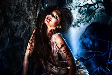 undead: Bloodthirsty zombi standing at the night cemetery in the mist and moonlight.