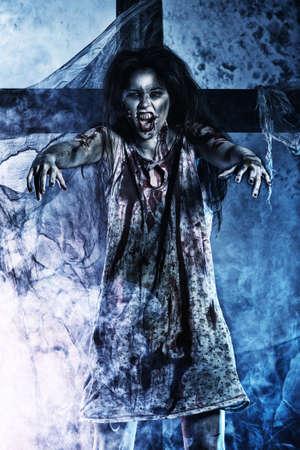 satanas: Zombi sanguinario de pie en el cementerio de la noche en la niebla y la luz de la luna.